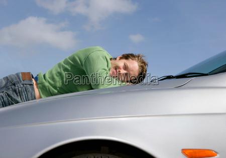 man lying on car