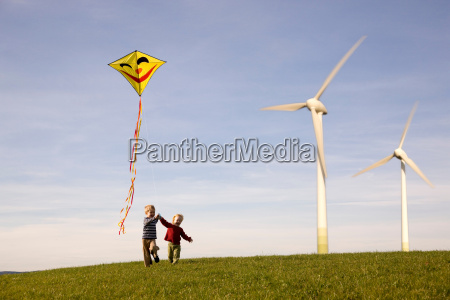 two boys flying kite at wind