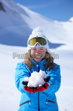 woman laughing holding snowball