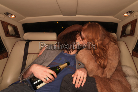 couple kissing on backseat of luxury