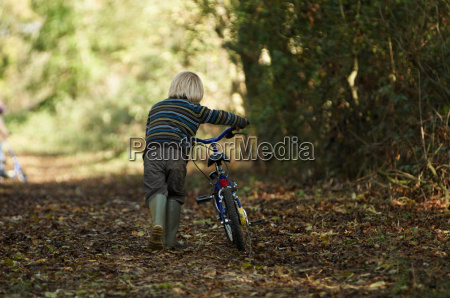 boy walking bike in countryside