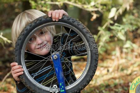 boy looking through bike wheel
