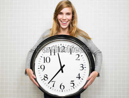 woman holding a big clock