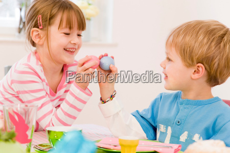 girl and boy painting eggs for