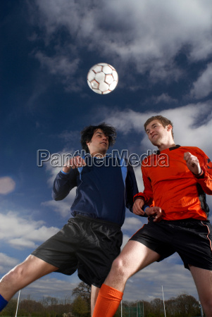 two footballers jumping for football