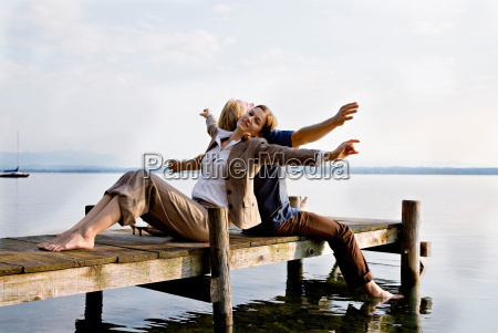 woman and man sitting on pier