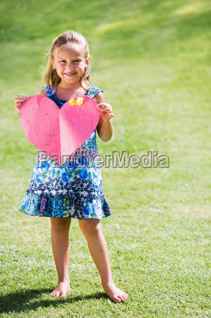 young girl holding red paper heart