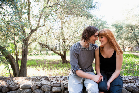 young couple sitting on wall