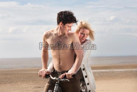 couple on beach on bike
