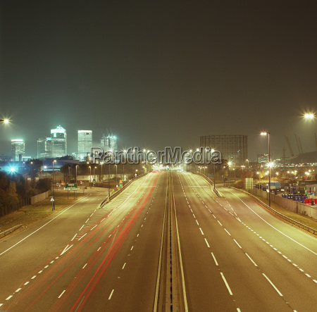 road leading towards cityscape at night