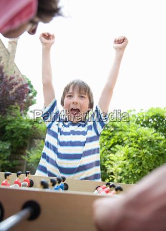 boy celebrating playing table football