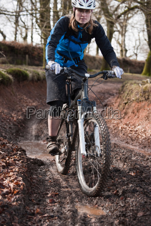 woman riding mountain bike muddy track