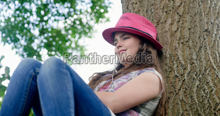 girl with headphones leaning on tree