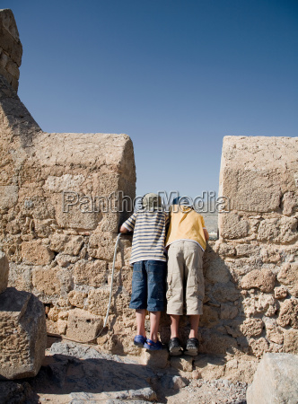 two boys looking over wall at