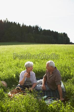 senior couple having picnic in meadows
