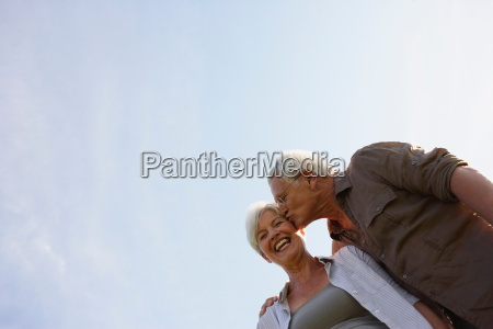 senior man kissing woman on cheek