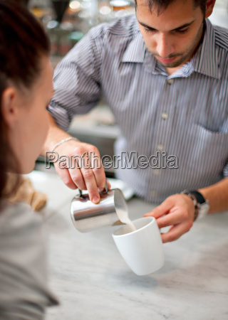 barkeeper making coffee for woman