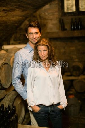 proud couple standing in wine cellar