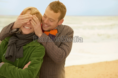 couple on beach his hands over