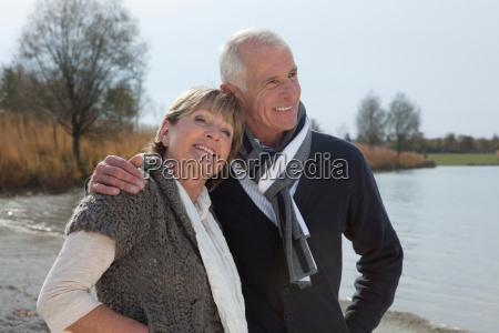 senior couple walking by lake