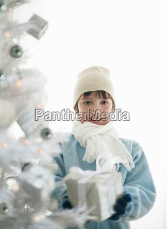 boy with present by xmas tree
