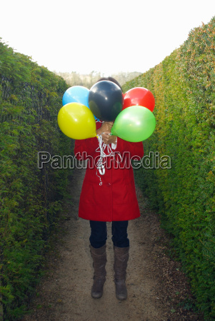 girl holding balloons in front of