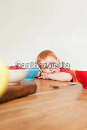 boy resting his head at dinner