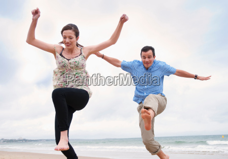 couple jumping on beach