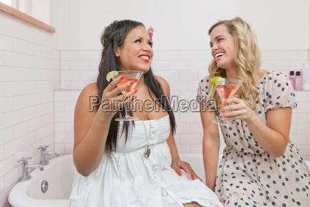 women drinking martinis in bathroom