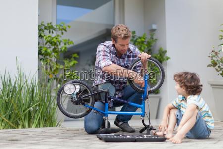 vater hilft sohn reparieren fahrrad