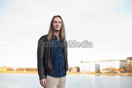 smiling man standing by urban lake