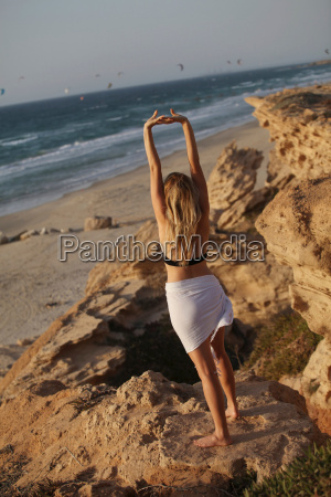 woman stretching on beach