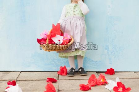 maedchen haelt korb von papierblumen