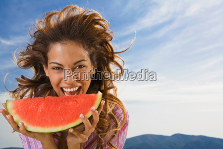 woman laughing and eating watermelon