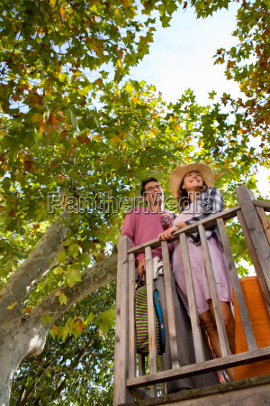 couple behind rail outdoors with bags