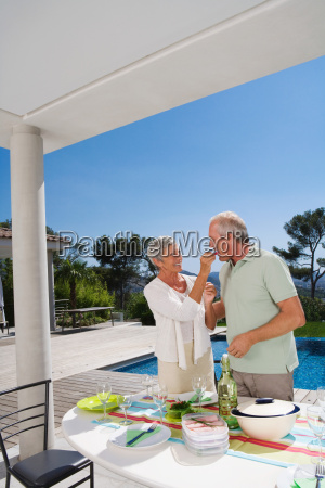 man and woman eating by poolside