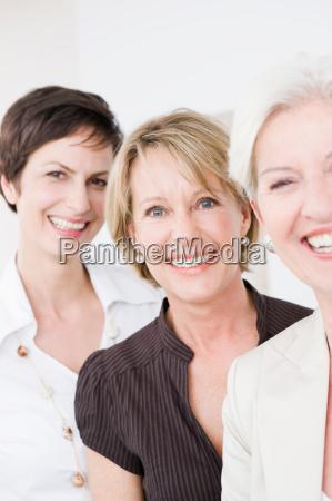 three women laughing into camera
