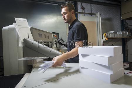 worker disposing of paper trimmings in