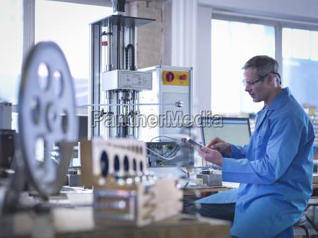 arbeiter in schutzbrille mit feder pruefgeraete