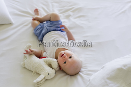 baby girl lying on bedclothes with