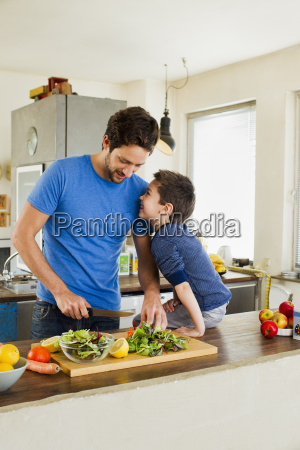 father and young son preparing vegetables