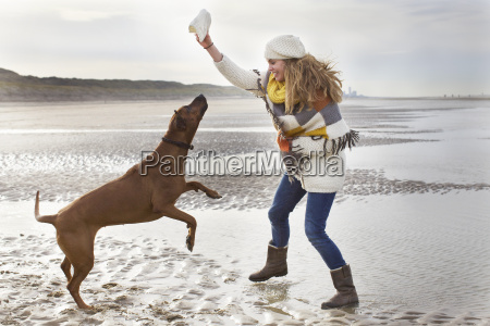 mid adult woman teasing dog at