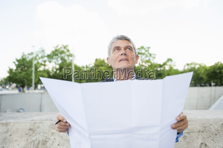 senior adult businessman holding plans