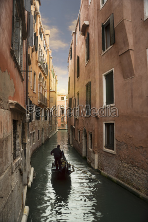 silhouetted gondolier on narrow canal venice