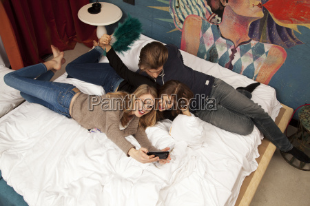 three adult friends lying on hotel