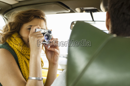 young woman photographing boyfriend driving cape