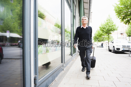 senior businessman hurriedly pulling wheeled suitcase