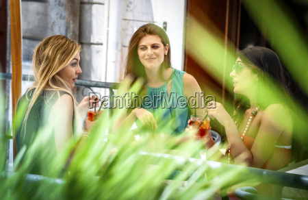 three young female friends having cocktails
