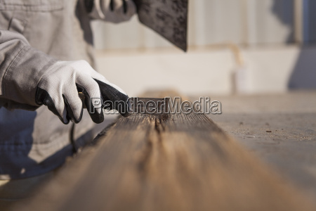 carpenter scraping wood plank in factory