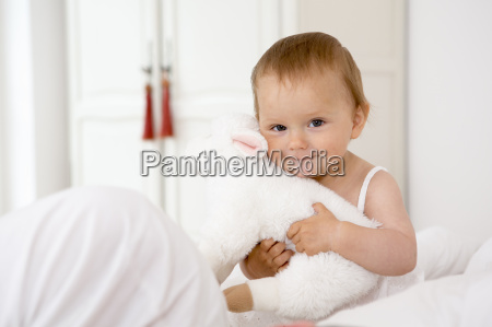 baby girl holding soft toy